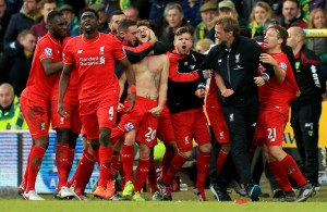 NORWICH, ENGLAND - JANUARY 23:  Adam Lallana (C) of Liverpool ceelbrates scoring his team's fifth goal with his team mates and manager Jurgen Klopp (2nd R) during the Barclays Premier League match between Norwich City and Liverpool at Carrow Road on January 23, 2016 in Norwich, England.  (Photo by Stephen Pond/Getty Images)